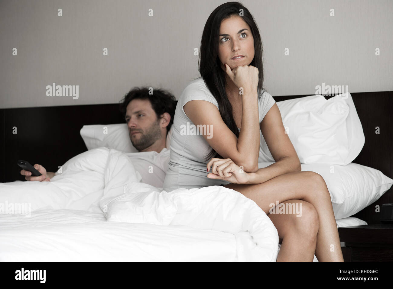 Woman sitting in bed while husband watching tv - Stock Image