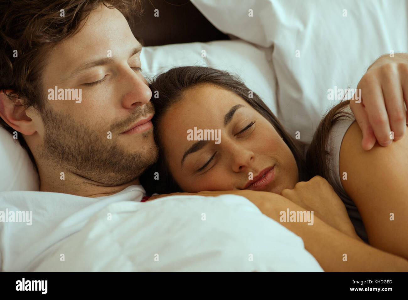 Couple resting and embracing in bed Stock Photo
