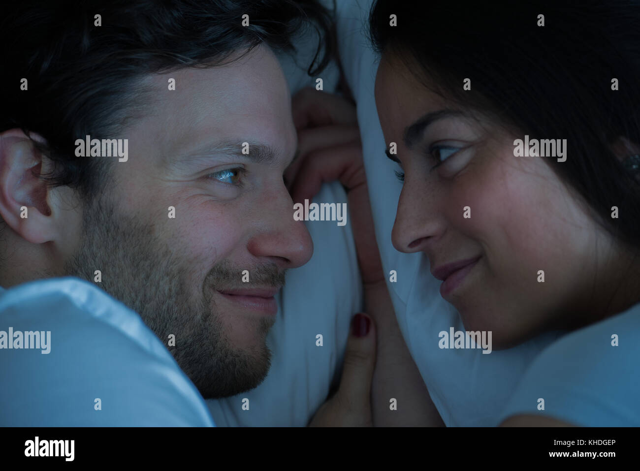 Couple lying in bed, looking at each other Stock Photo