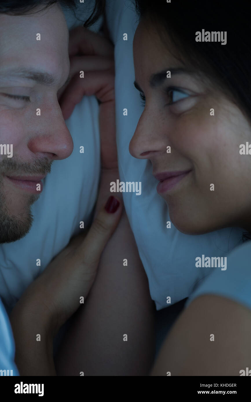 Couple lying in bed together Stock Photo