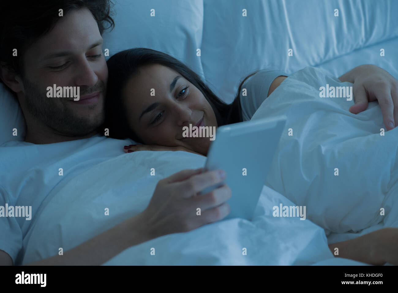 Couple using digital tablet in bed Stock Photo
