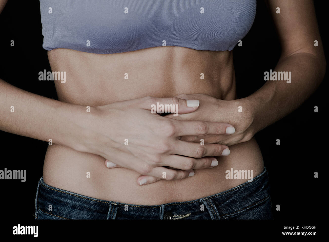 Woman clutching bare stomach with hands Stock Photo