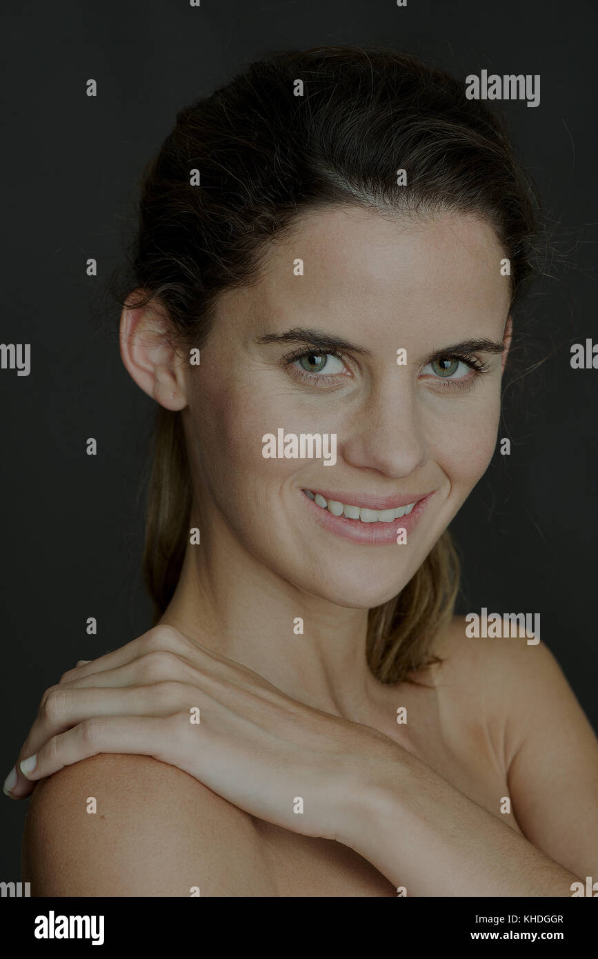 Young woman with hand on bare shoulder, smiling, portrait Stock Photo