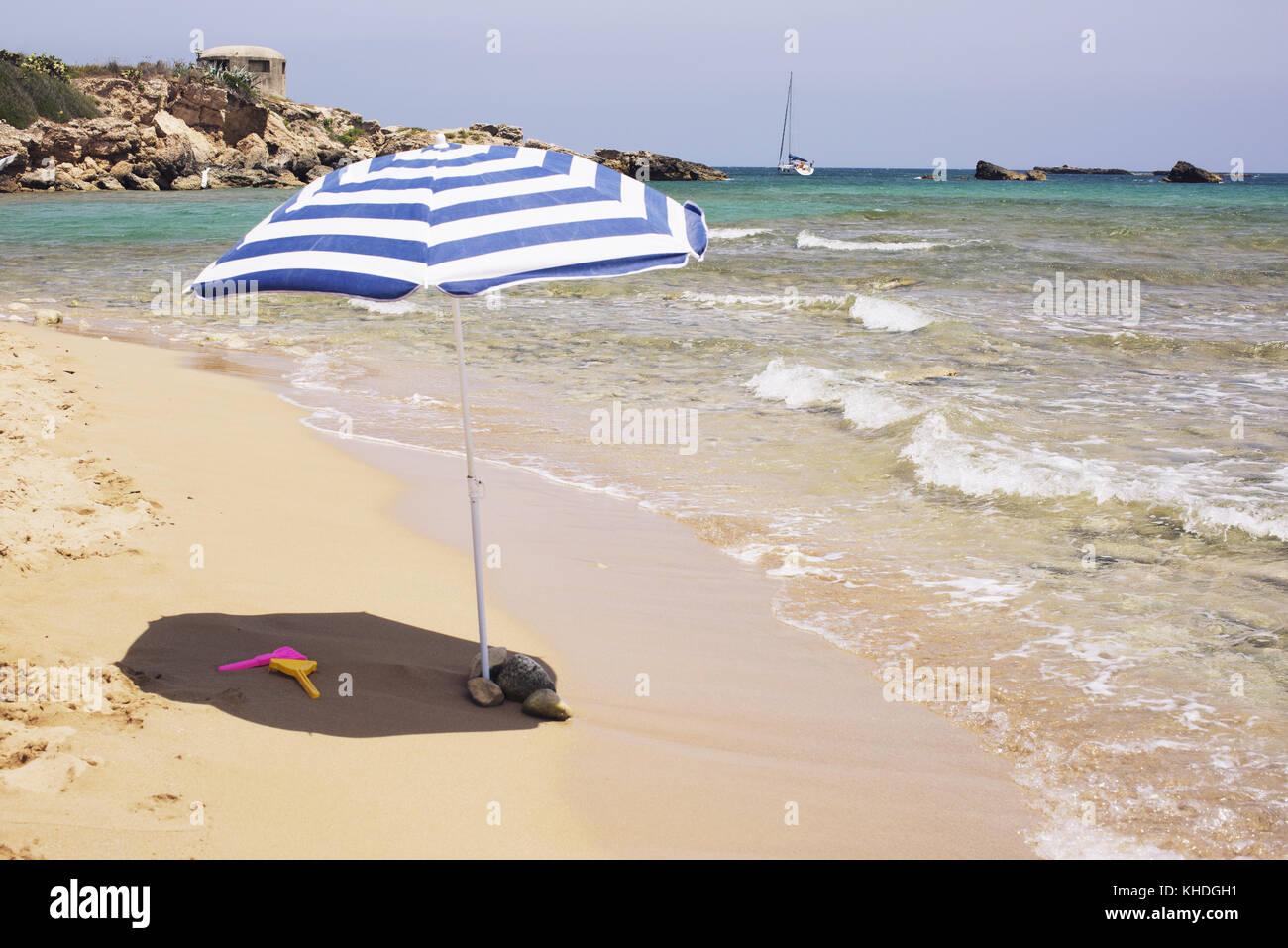 Parasol on beach near water's edge Stock Photo