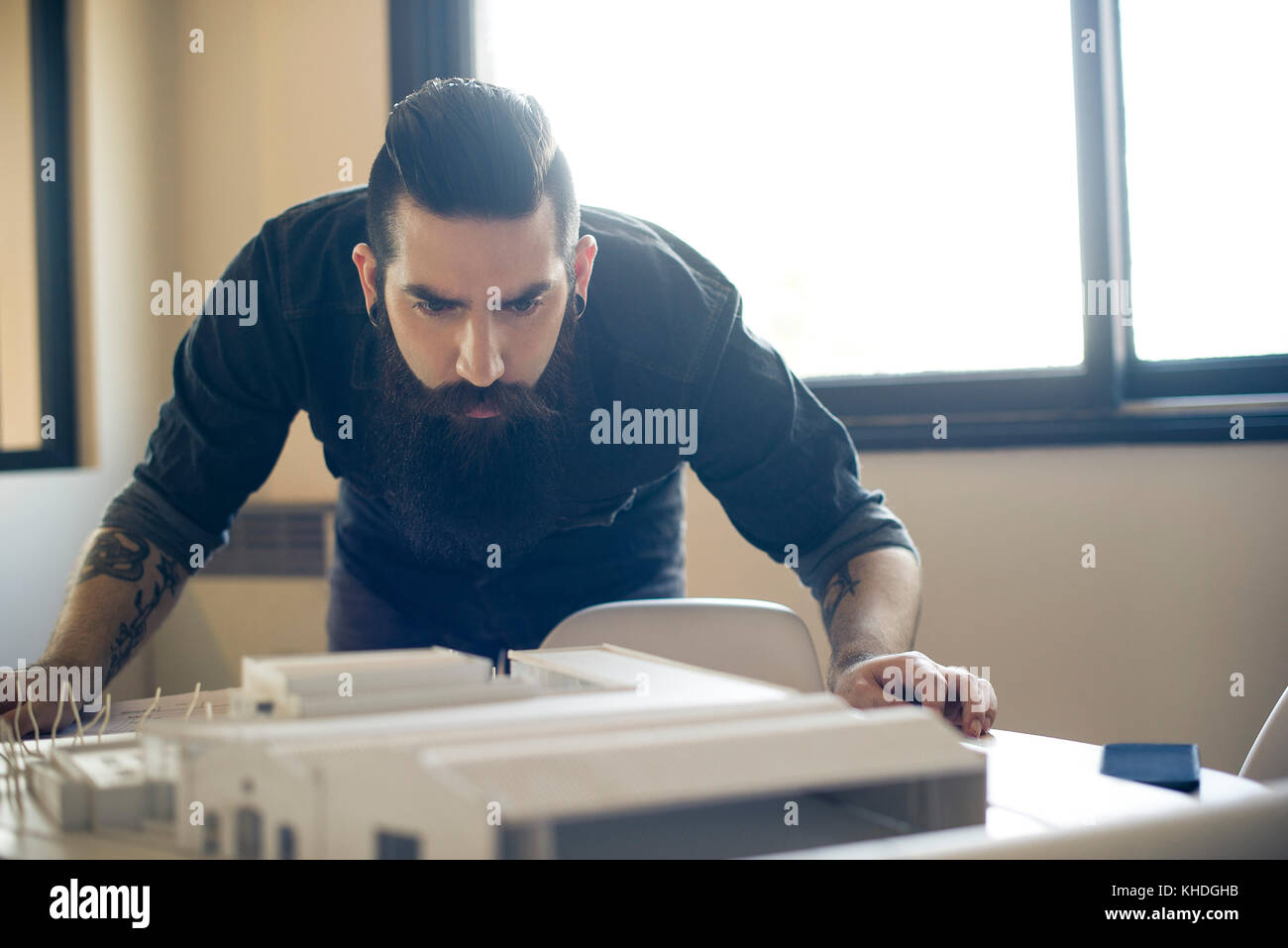Architect looking at model building Stock Photo