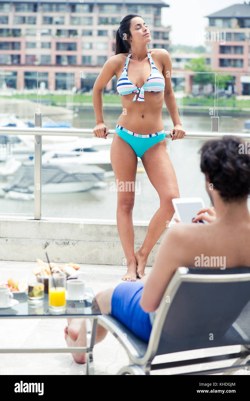 Woman sunbathing, man relaxing by pool using digital tablet - Stock Image