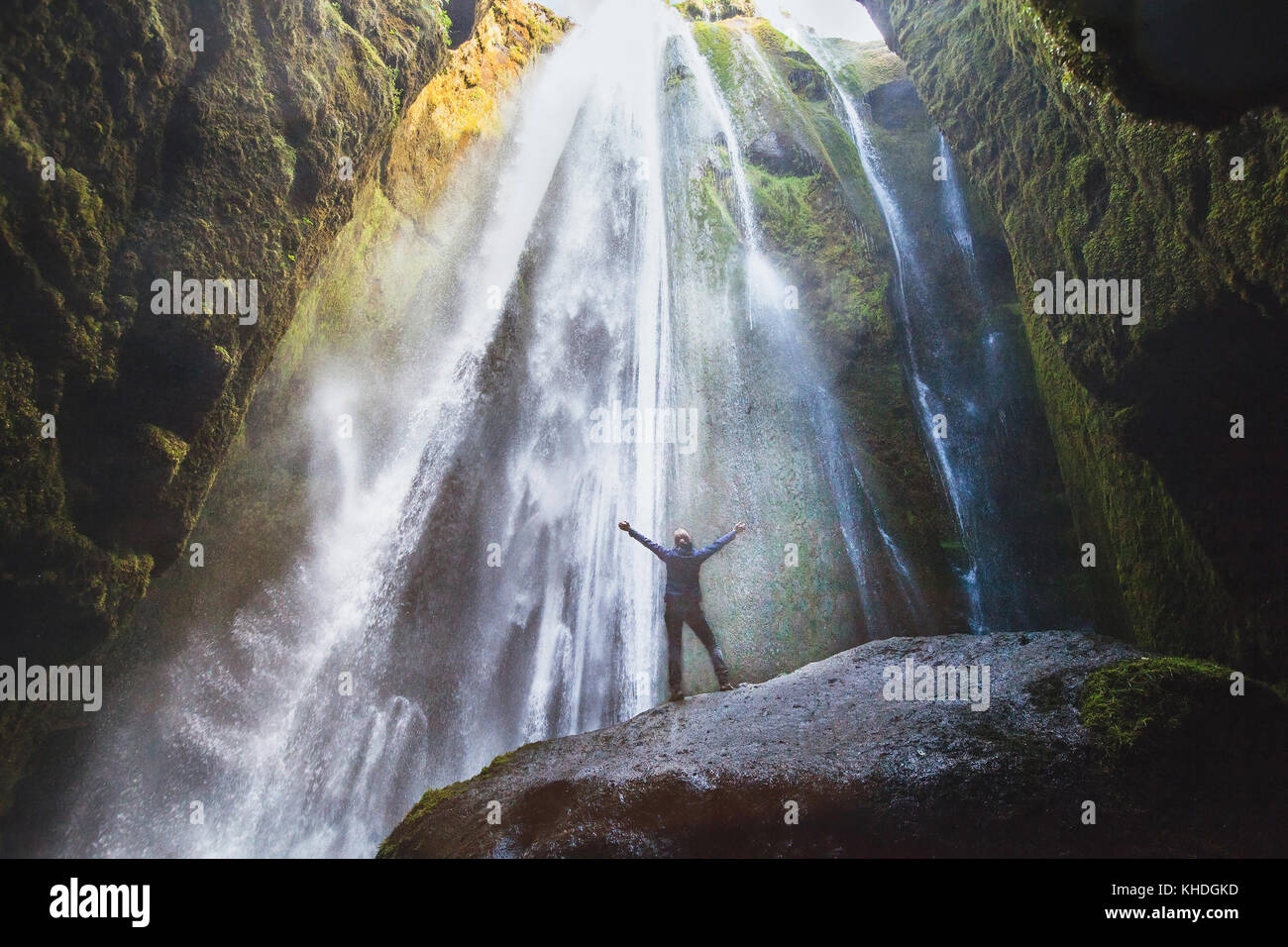 travel to Iceland, person with raised hands standing in waterfall Gljufrabui, inspired happy traveler enjoying nature, - Stock Image