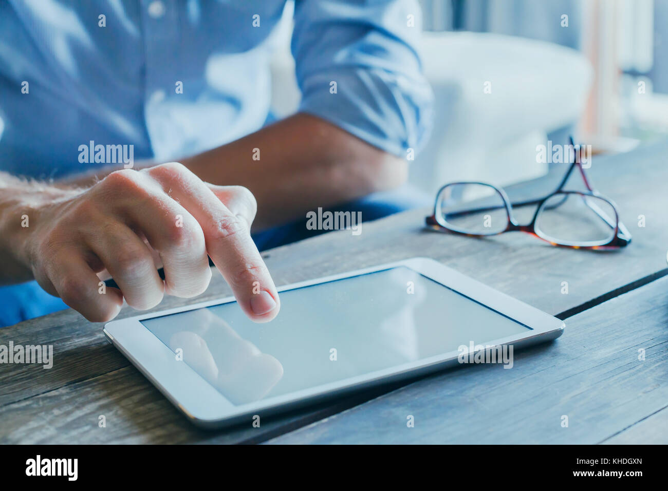 man reading emails and news on social media, close up of hands using digital tablet computer, banking online - Stock Image