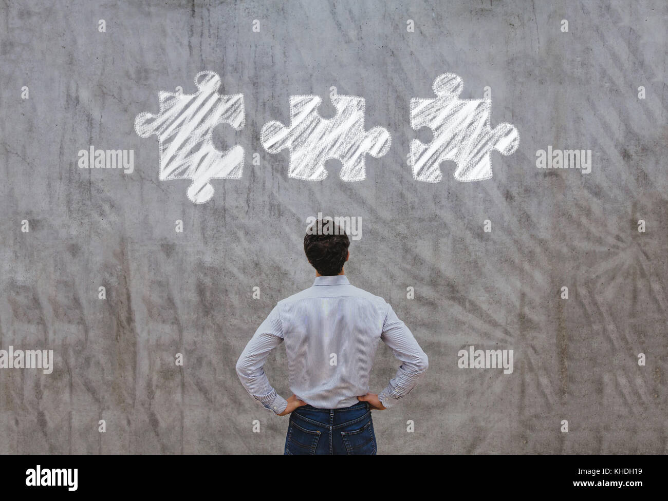 business man looking at the pieces of puzzle, complex solution concept - Stock Image