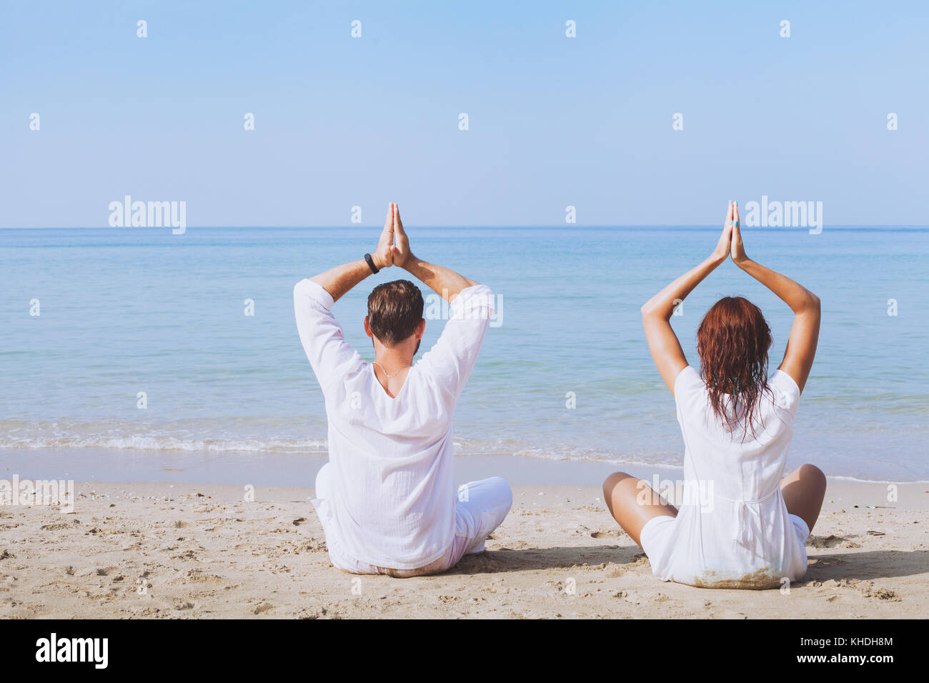 yoga on the beach, two people in white clothes practicing meditation, healthy lifestyle background - Stock Image