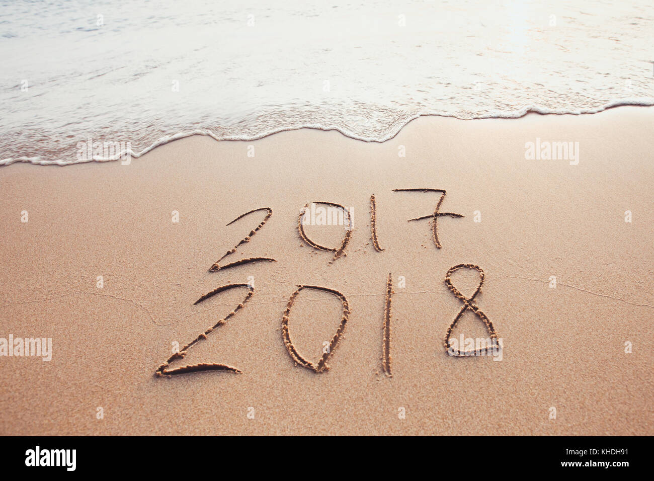 new year change 2017 to 2018, calendar dates written on the sand of beach - Stock Image