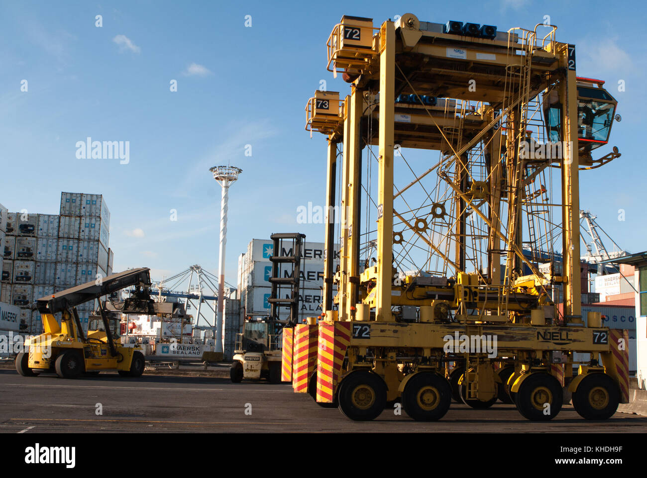 AUCKLAND, NEW ZEALAND - 17th APRIL 2012: Noell straddle carriers and stack of containers at port of Auckland. - Stock Image