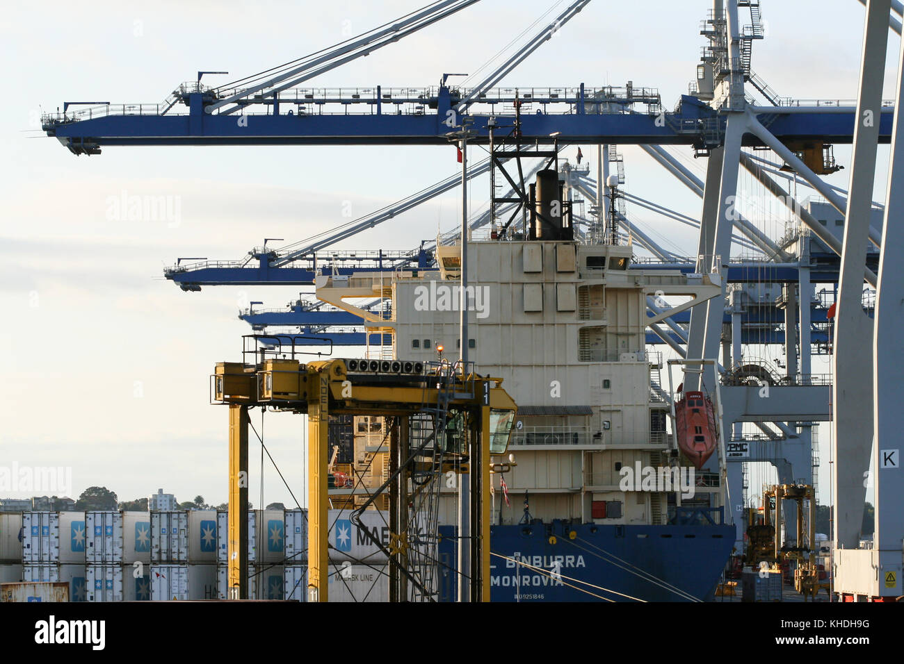 AUCKLAND, NEW ZEALAND - 17th APRIL 2012: Vessel, wheeled cranes and stack of containers at Auckland sea port. - Stock Image