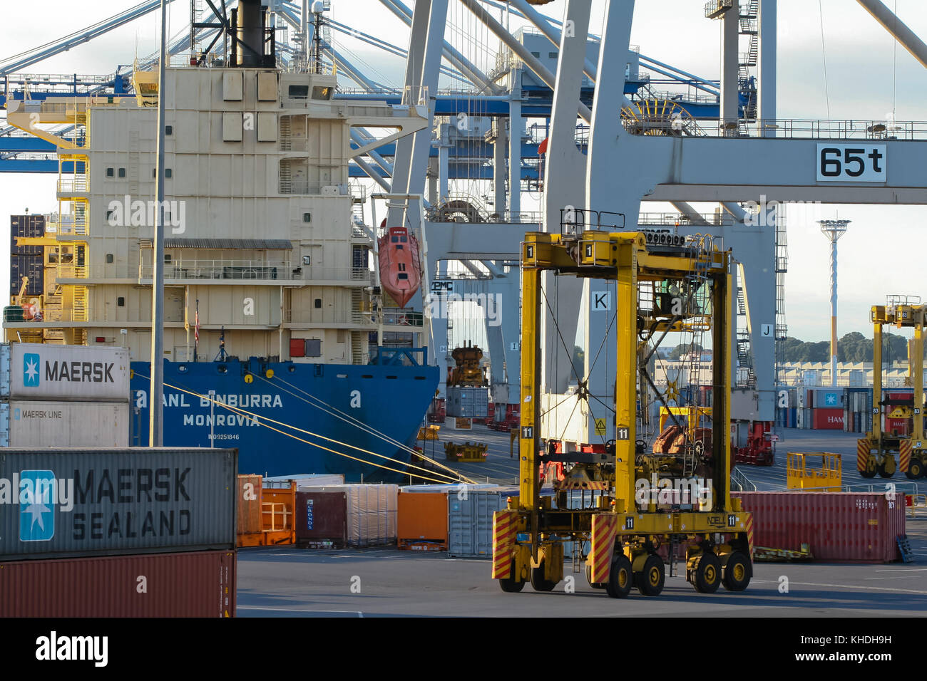 AUCKLAND, NEW ZEALAND - 17th APRIL 2012: Vessel, straddle carriers, wheeled cranes and stack of containers at Auckland - Stock Image