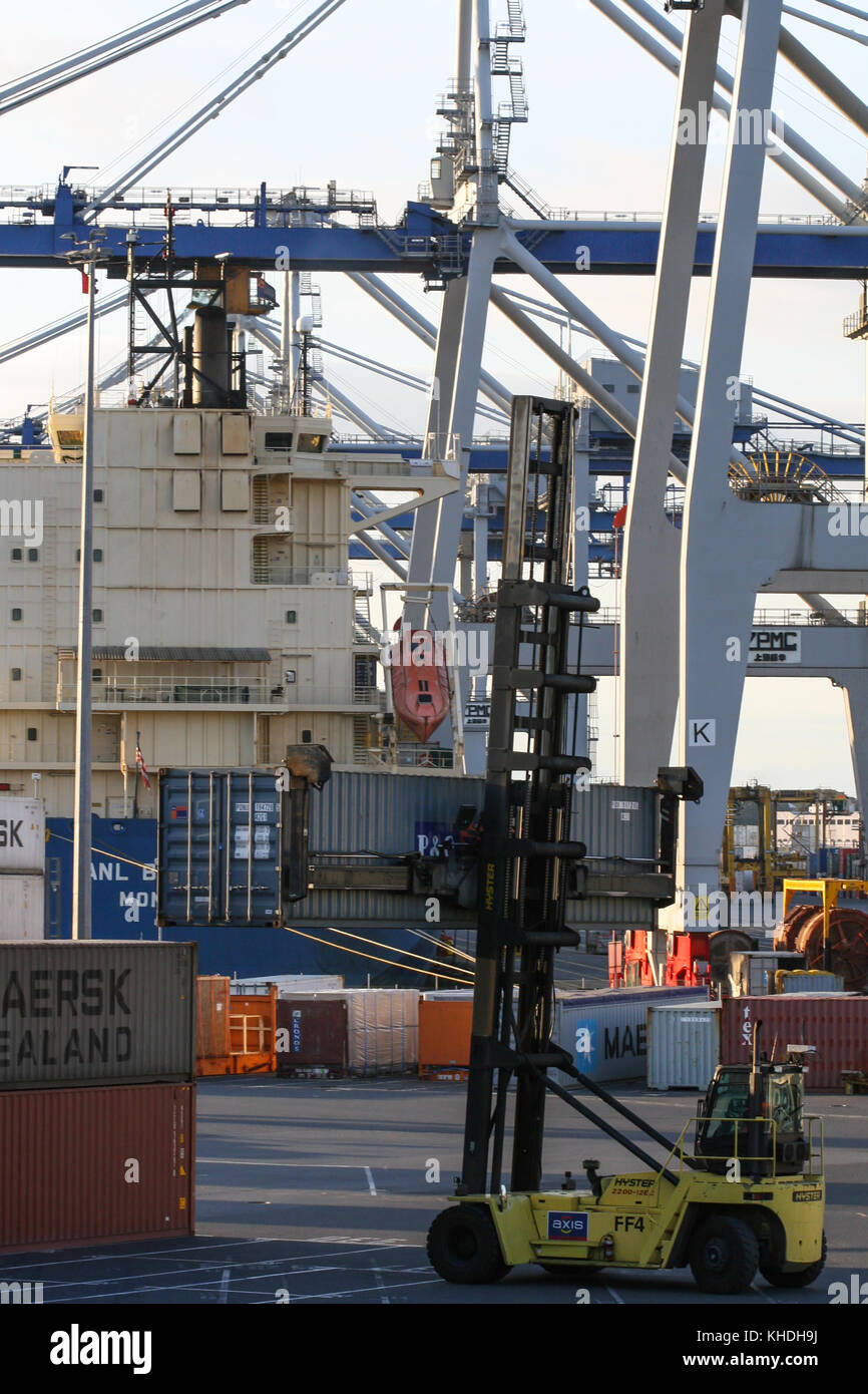 AUCKLAND, NEW ZEALAND - 17th APRIL 2012: Wheeled cranes and carrier truck holding a container at Auckland sea port. - Stock Image