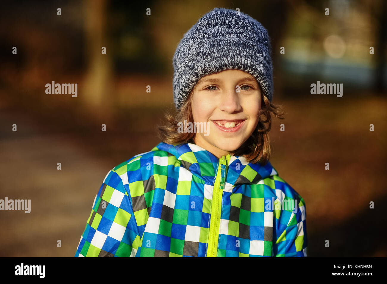 Portrait of a smiling boy of 9-10 years. The boy is dressed in a colorful jacket and a knitted cap. - Stock Image
