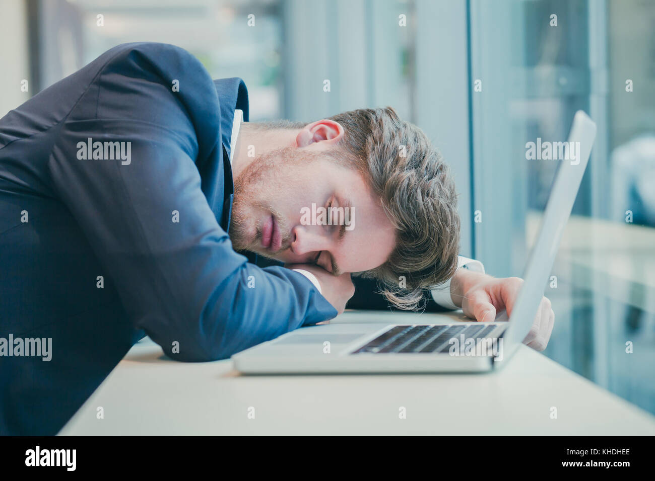 tired businessman sleeping near computer - Stock Image