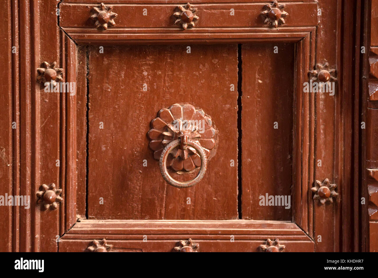 Old doorknob on vintage red door in India - Stock Image