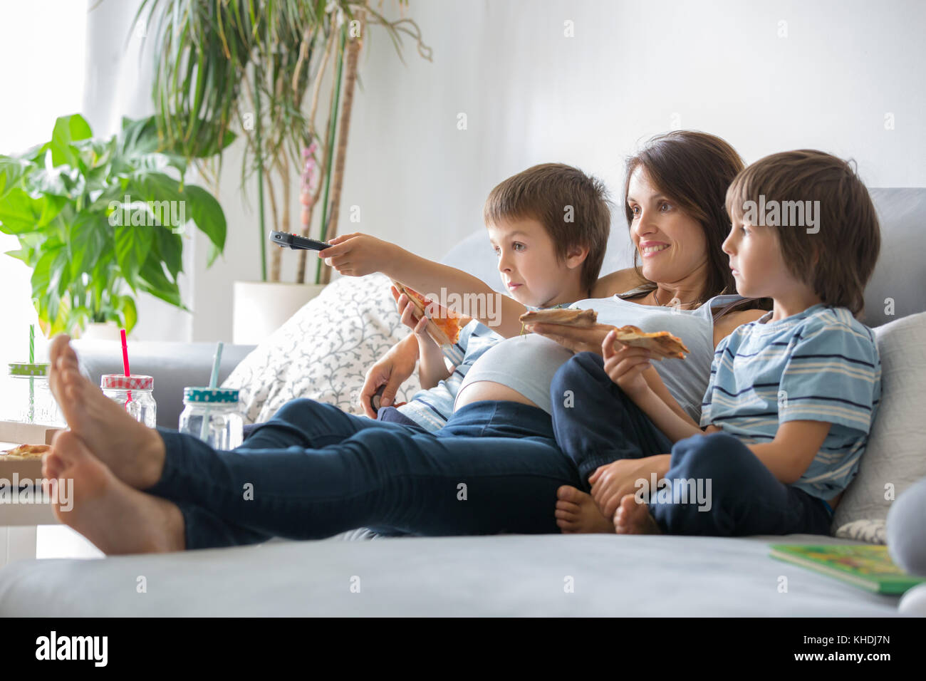 Happy young family, pregnant mother and two boys, eating tasty pizza at home, sitting on the sofa, watching TV and - Stock Image