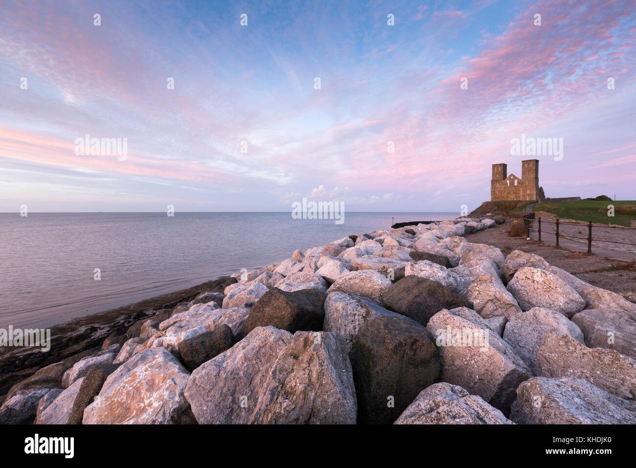 A vivid pink sunset at Reculver Towers, the Medieval church at Reculver on the north Kent coast, UK. The rocks in Stock Photo