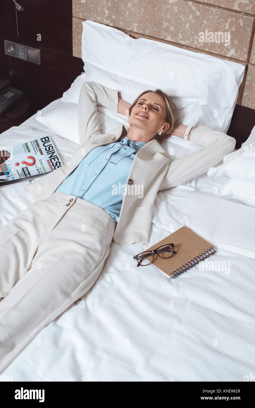 happy businesswoman on bed in hotel - Stock Image