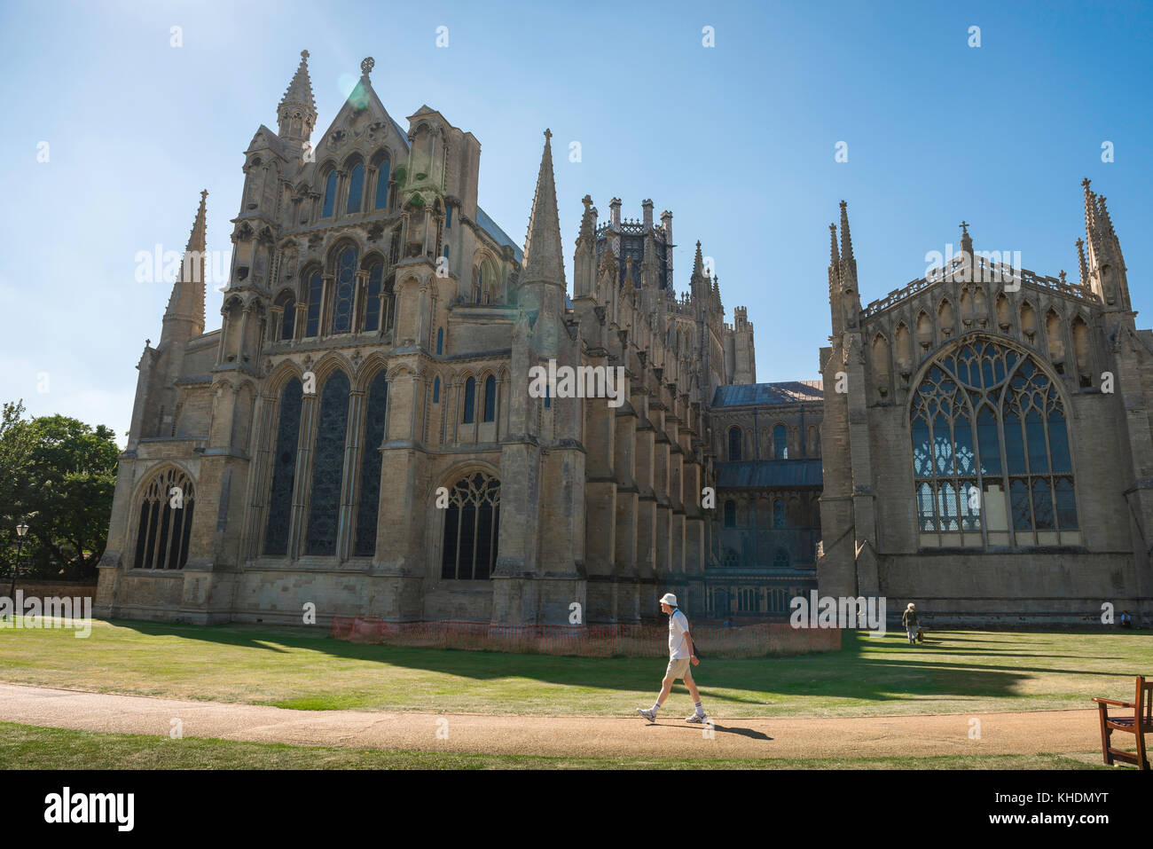 Ely Cathedral UK, a visitor to Ely walks past the east end of the city's medieval cathedral, Cambridgeshire, - Stock Image