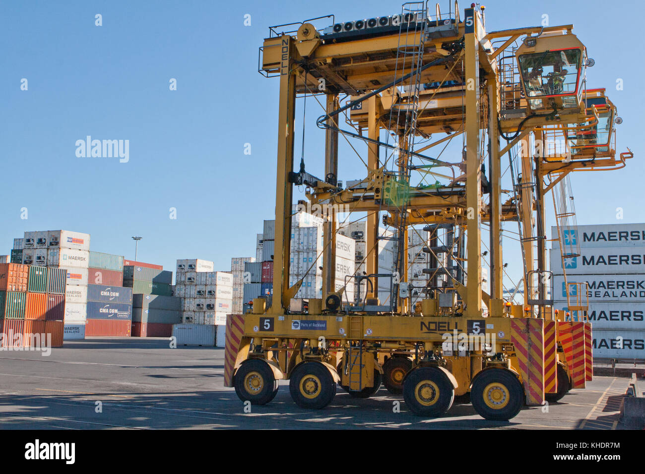 AUCKLAND, NEW ZEALAND - APRIL 19 2012: Straddle carriers and stack of containers at Auckland port. New Zealand - Stock Image