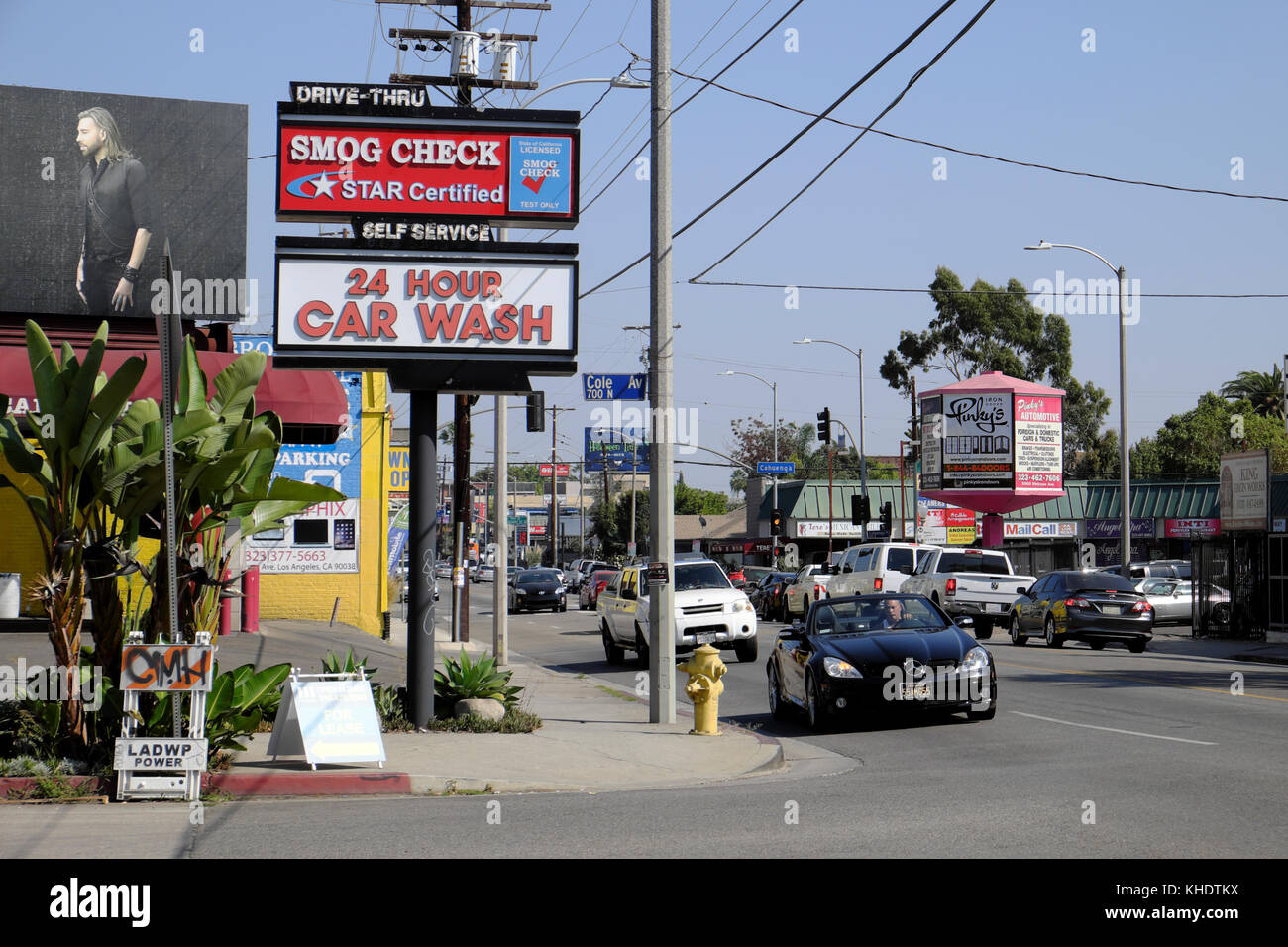 Convertible car and traffic on Melrose Avenue near Cole Ave and Smog Check 24 hour Car Wash sign Hollywood, Los - Stock Image