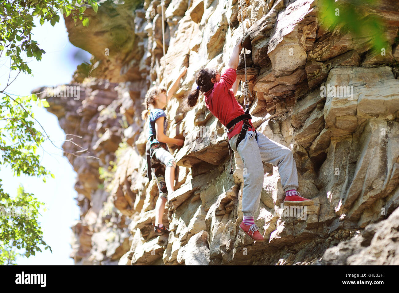 Two teenage girls are engaged in rock climbing - Stock Image