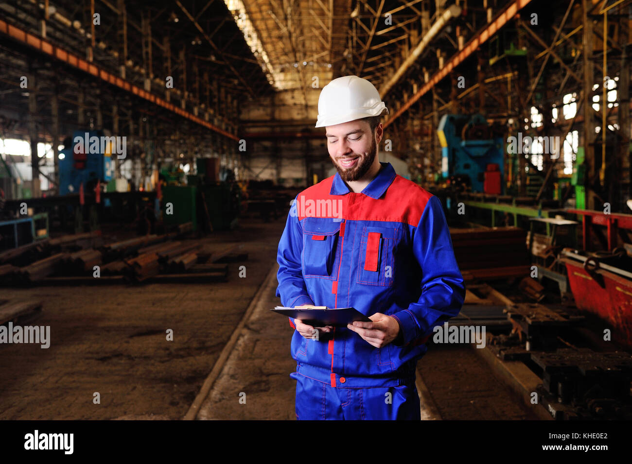 Worker in a helmet with a tablet - Stock Image
