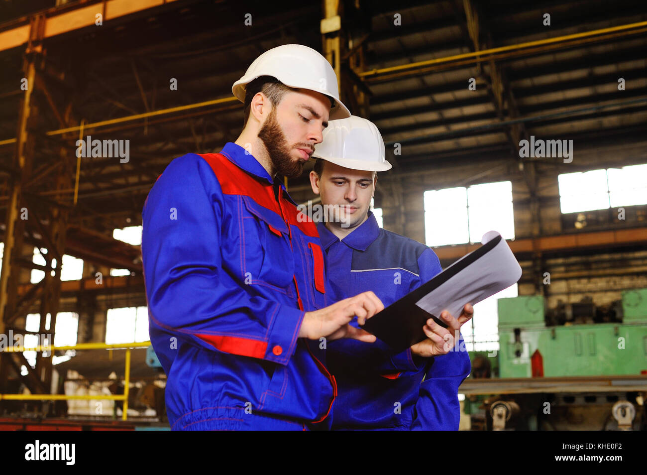 Two workers discuss a construction project - Stock Image