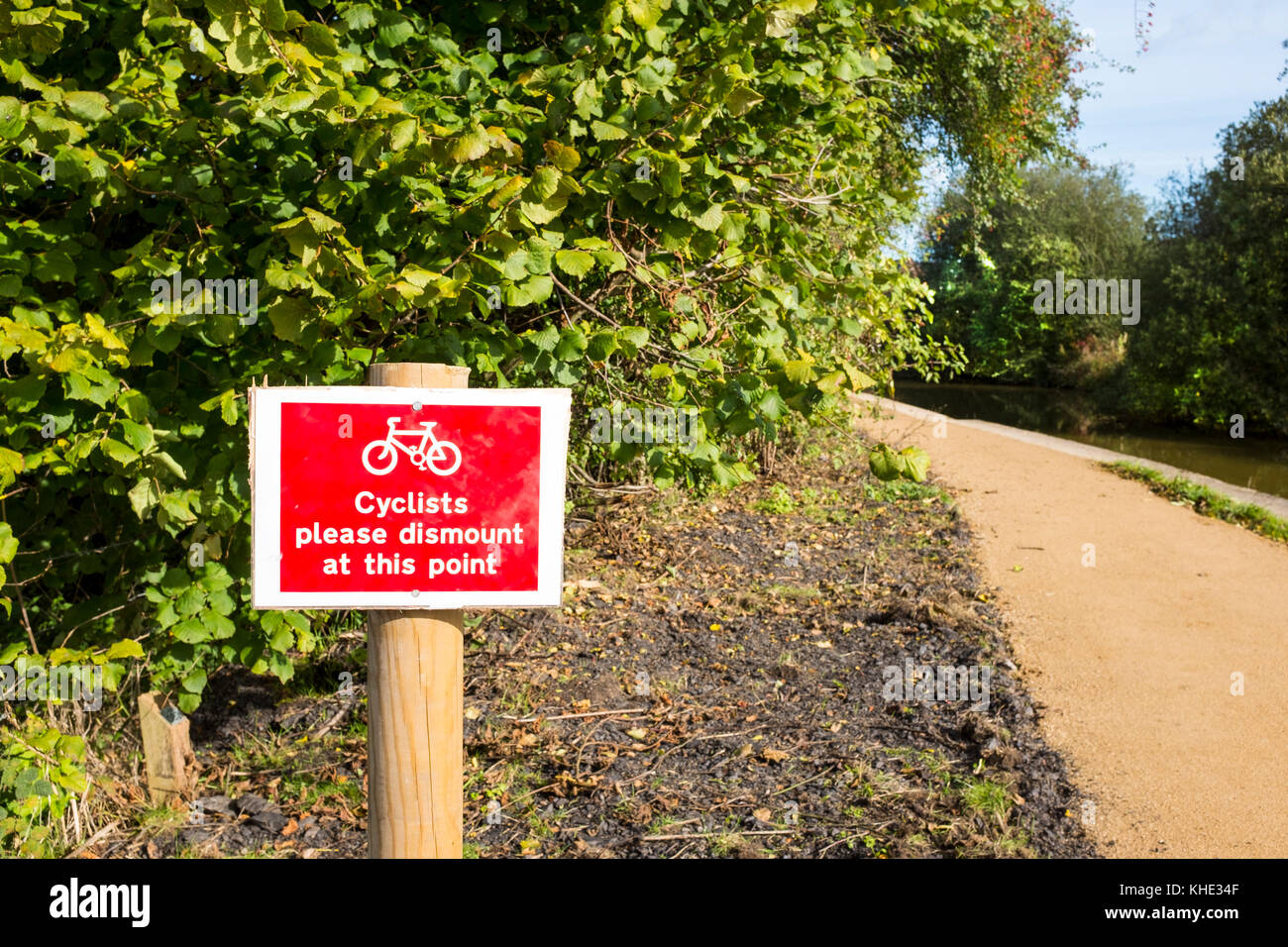Cyclists please dismount at this point sign on towpath, Trent and Mersey Canal in Cheshire UK - Stock Image