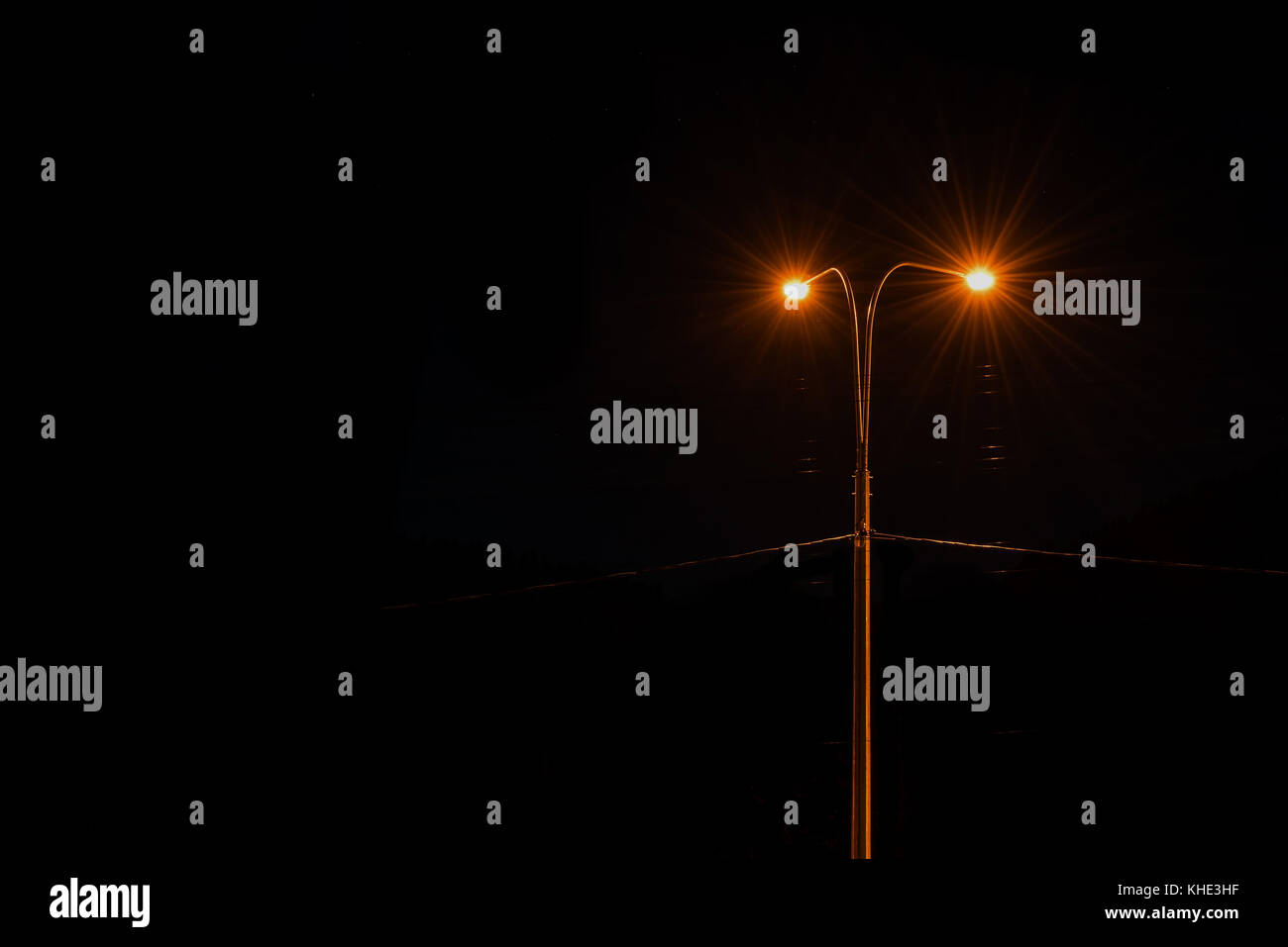 High urban street light shines against the night black sky - Stock Image