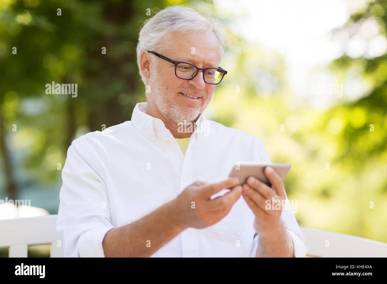 senior man with smartphone at summer park - Stock Image