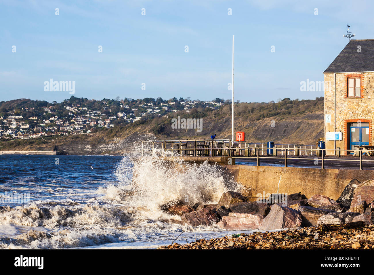 Waves breaking against the quay at Charmouth in Dorset. - Stock Image