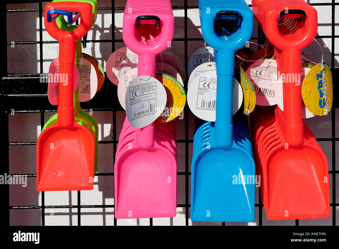 Brightly coloured plastic toy spades on display outside a shop in Lyme Regis in Dorset. - Stock Image