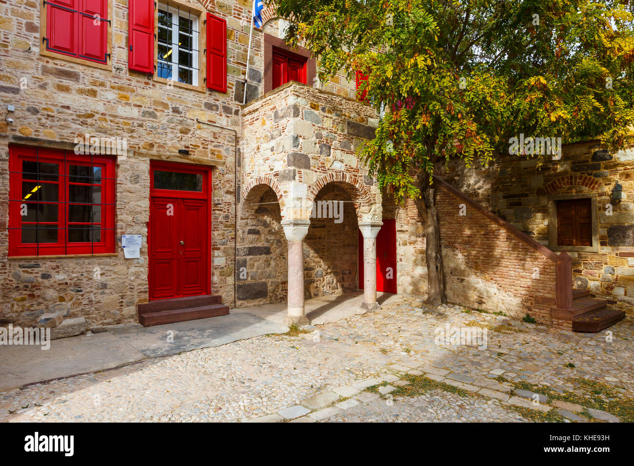 Architecture in the old town of Chios with red doors and windows. - Stock Image