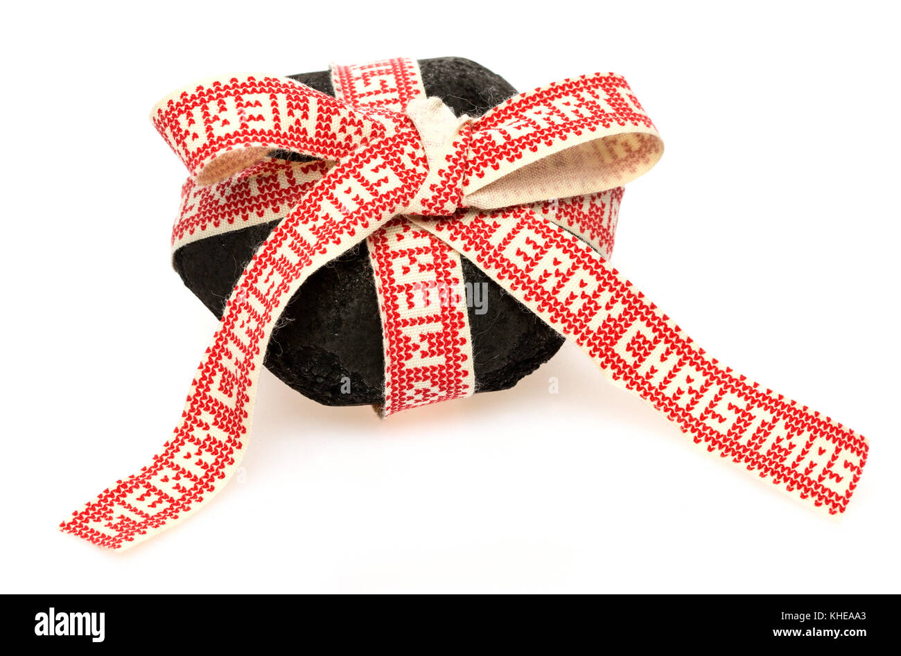 A piece of coal wrapped for a Christmas present - Stock Image