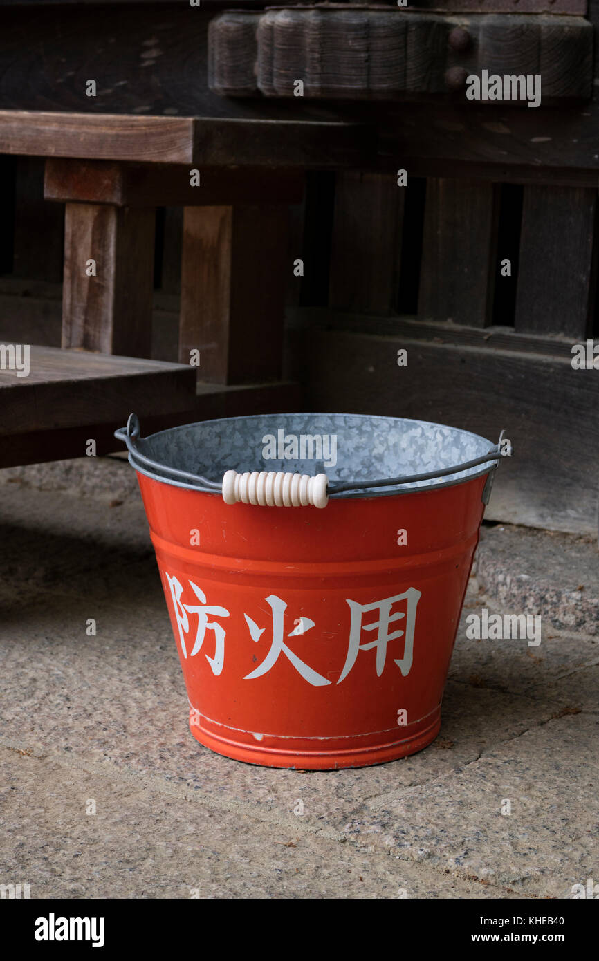 Nara, Japan -  May 31, 2017: Traditional red fire bucket with water in front of the wooden temple as fire prevention - Stock Image