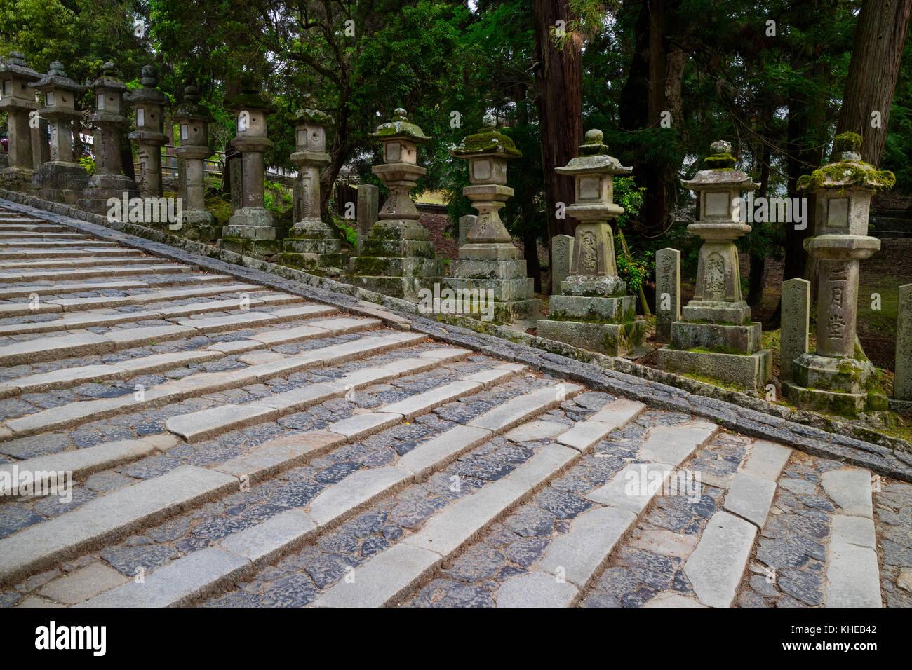 Nara - Japan, May 31, 2017: Row of many stone lanterns that lead up to the Kasuga Taisha shrine - Stock Image