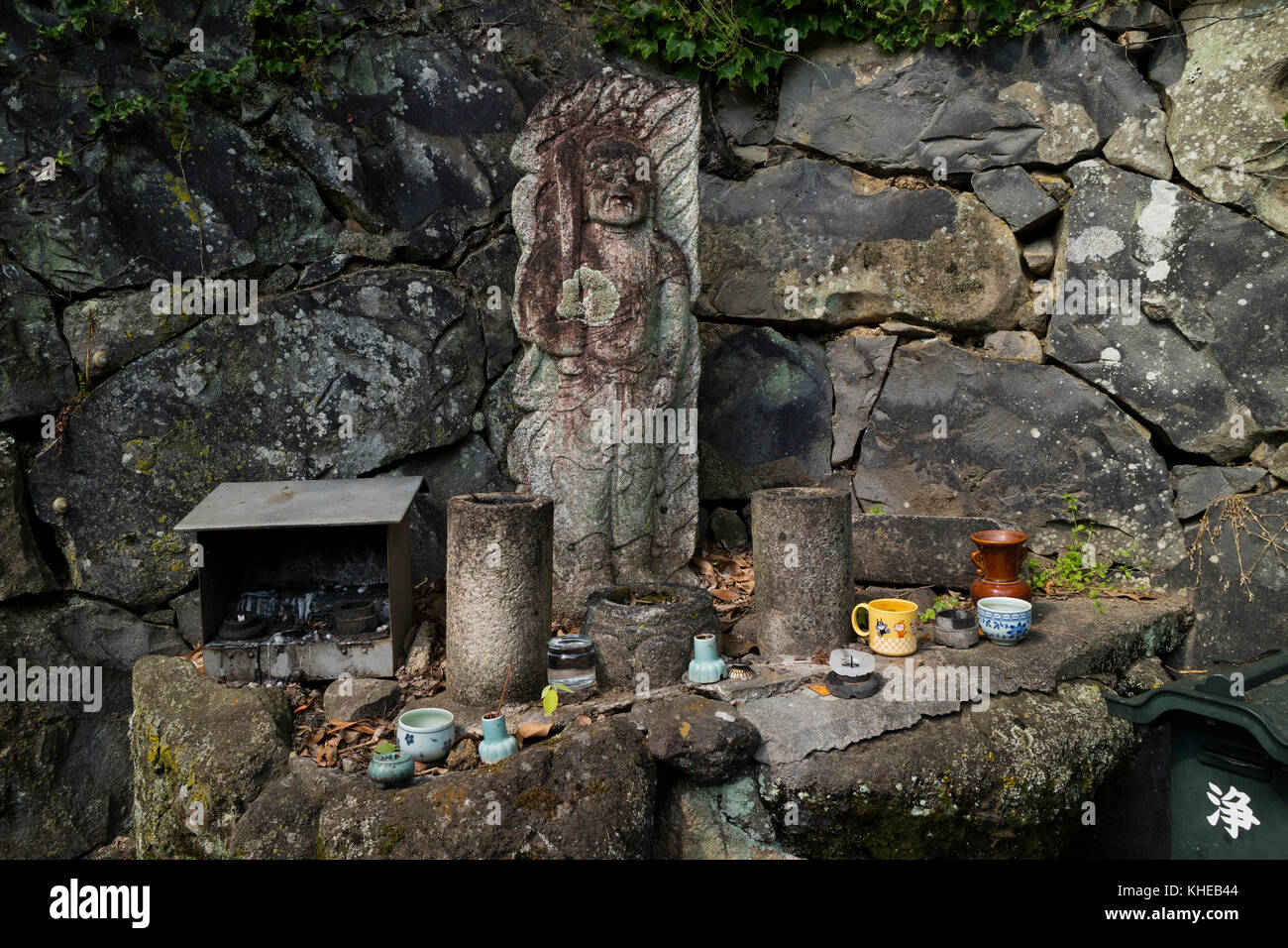 Nara, Japan -  May 31, 2017: Old stone sculpture honoured with cups of water and incense in the Kasugayama Primeval - Stock Image