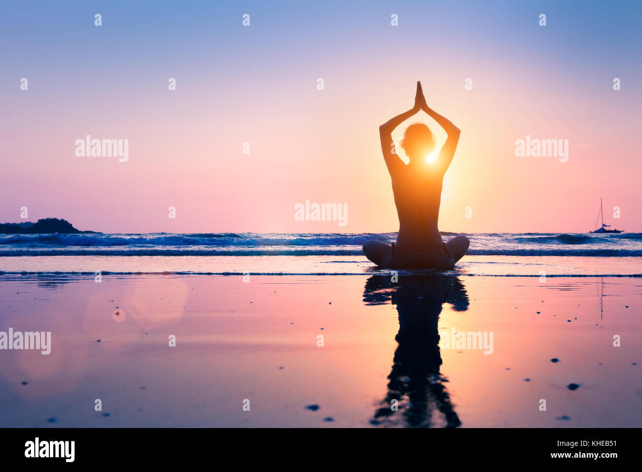Silhouette of young woman practicing yoga, lotus position, and meditating on the beach - Stock Image