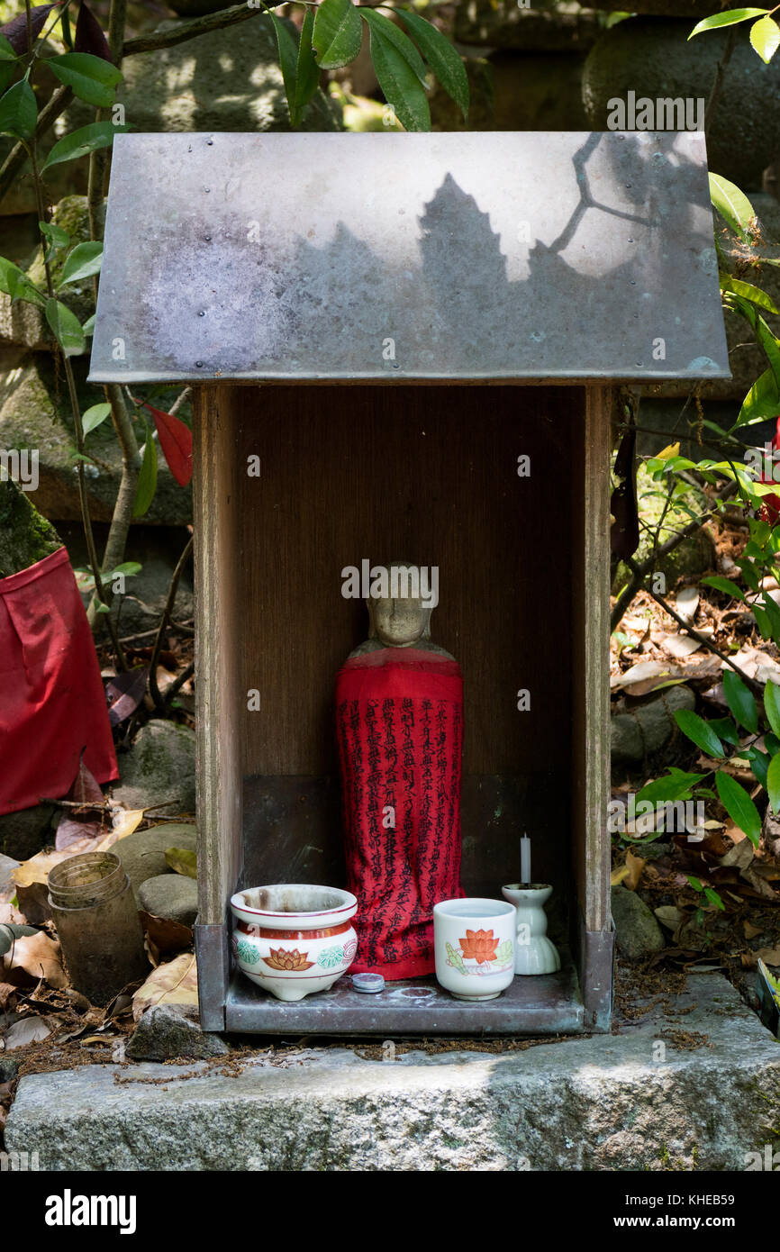 Iga Ueno - Japan, June 1, 2017: Traditional stone carved Jizo with red skirt honored and respected with a cup of - Stock Image