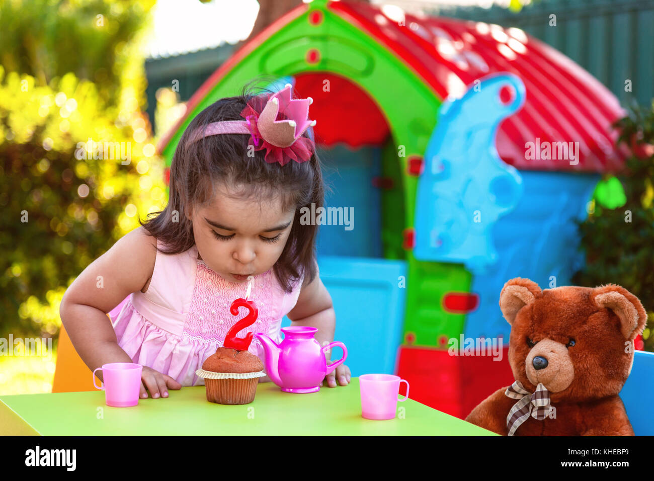 Baby toddler girl in outdoor second birthday party blowing candle on muffin. Teddy Bear as best friend, playhouse - Stock Image
