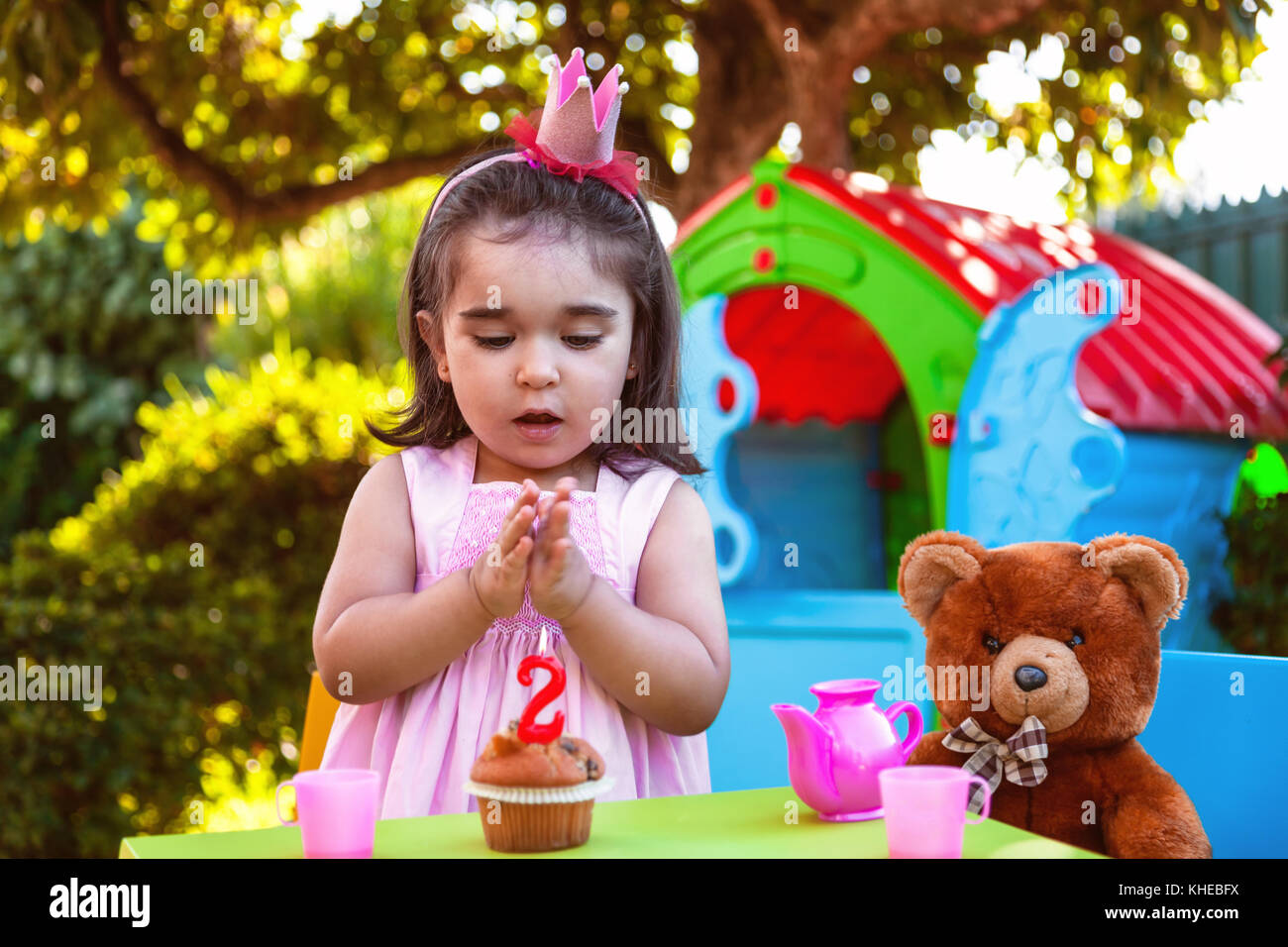 Baby toddler girl in outdoor second birthday party clapping hands at cake with Teddy Bear as best friend, playhouse - Stock Image