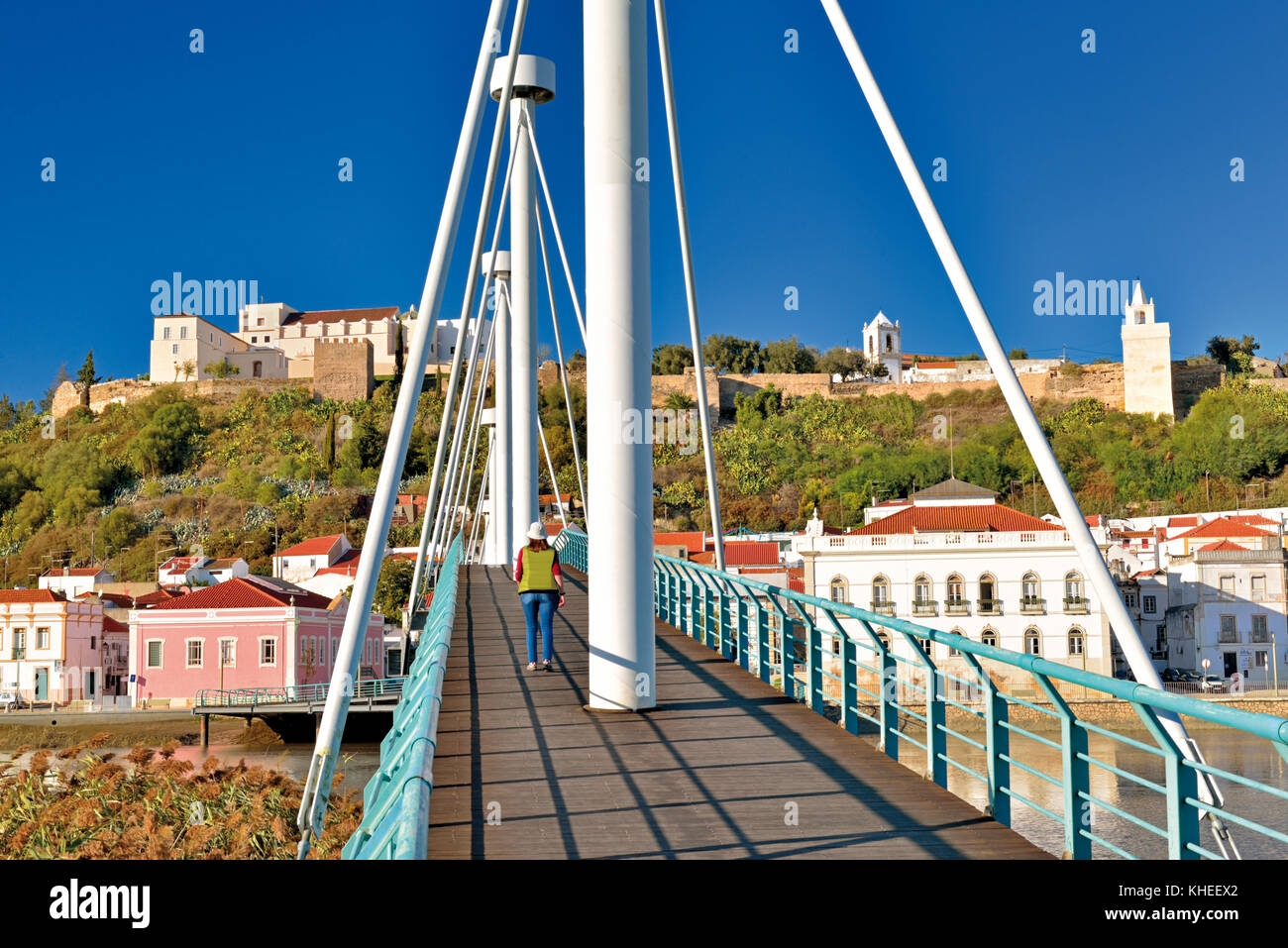 Woman crossing modern pedestrian bridge towards historic center of Alcacer do Sal, Alentejo, Portugal - Stock Image