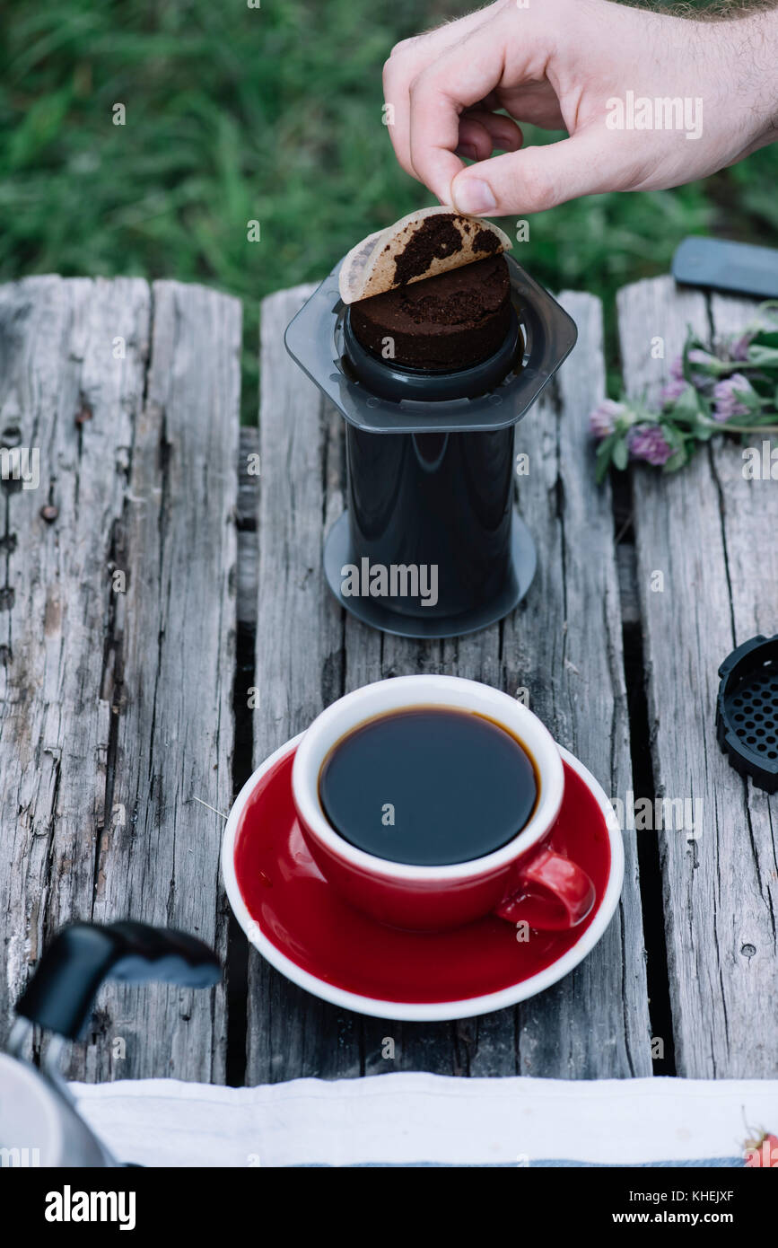 Fresh coffee puck, left from making filter coffee outdoors on the wooden table background - Stock Image