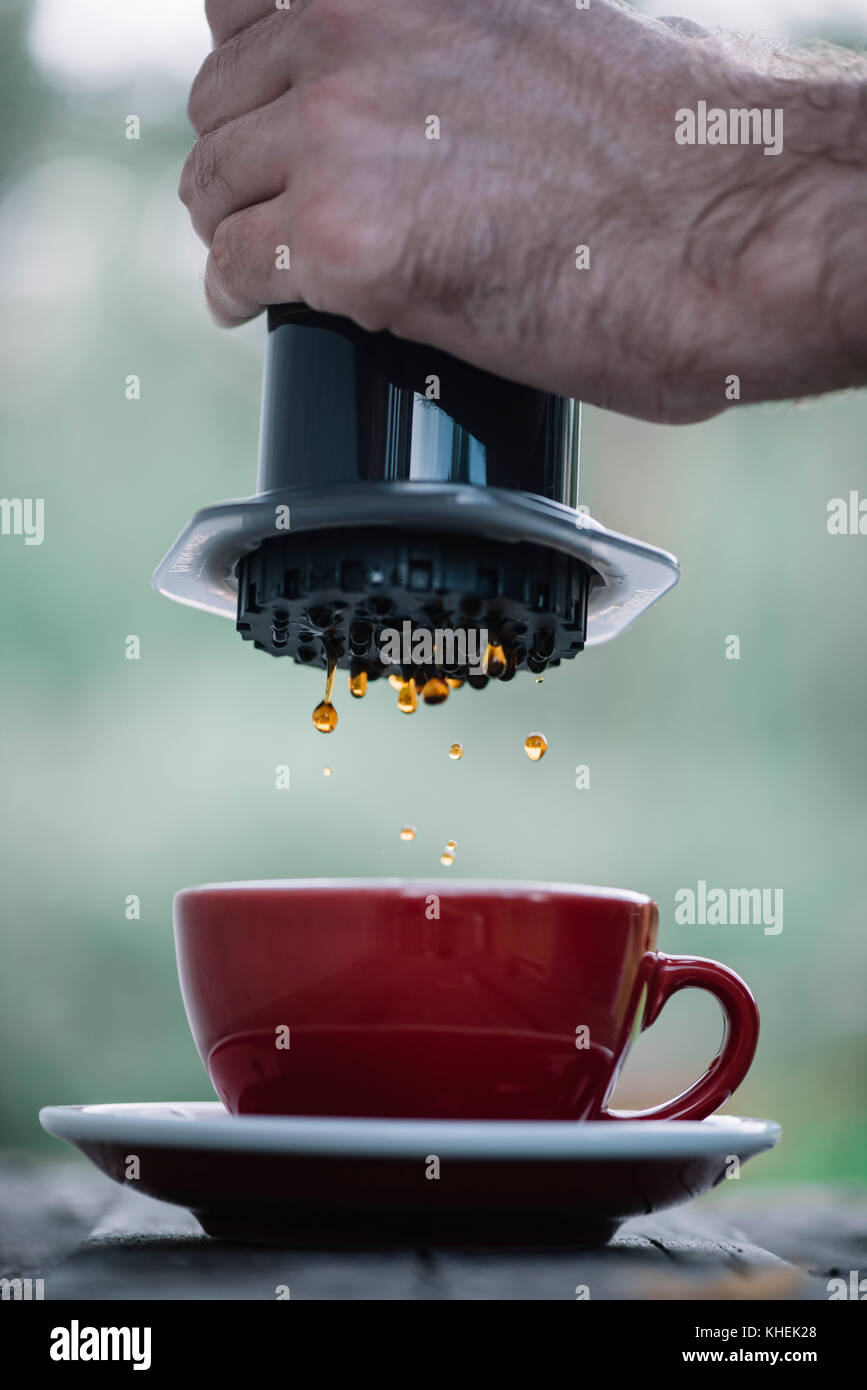 Delicious fresh morning pourover coffee dripping into ceramic red cup from the coffee maker - Stock Image