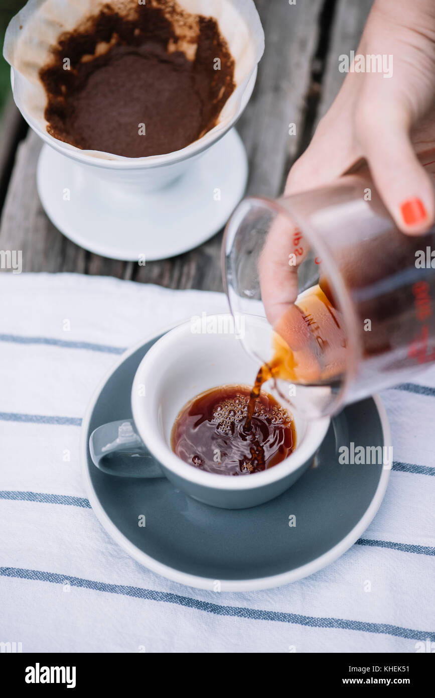 Delicious freshly brewed pour over coffee pouring into porcelain coffee cup - Stock Image