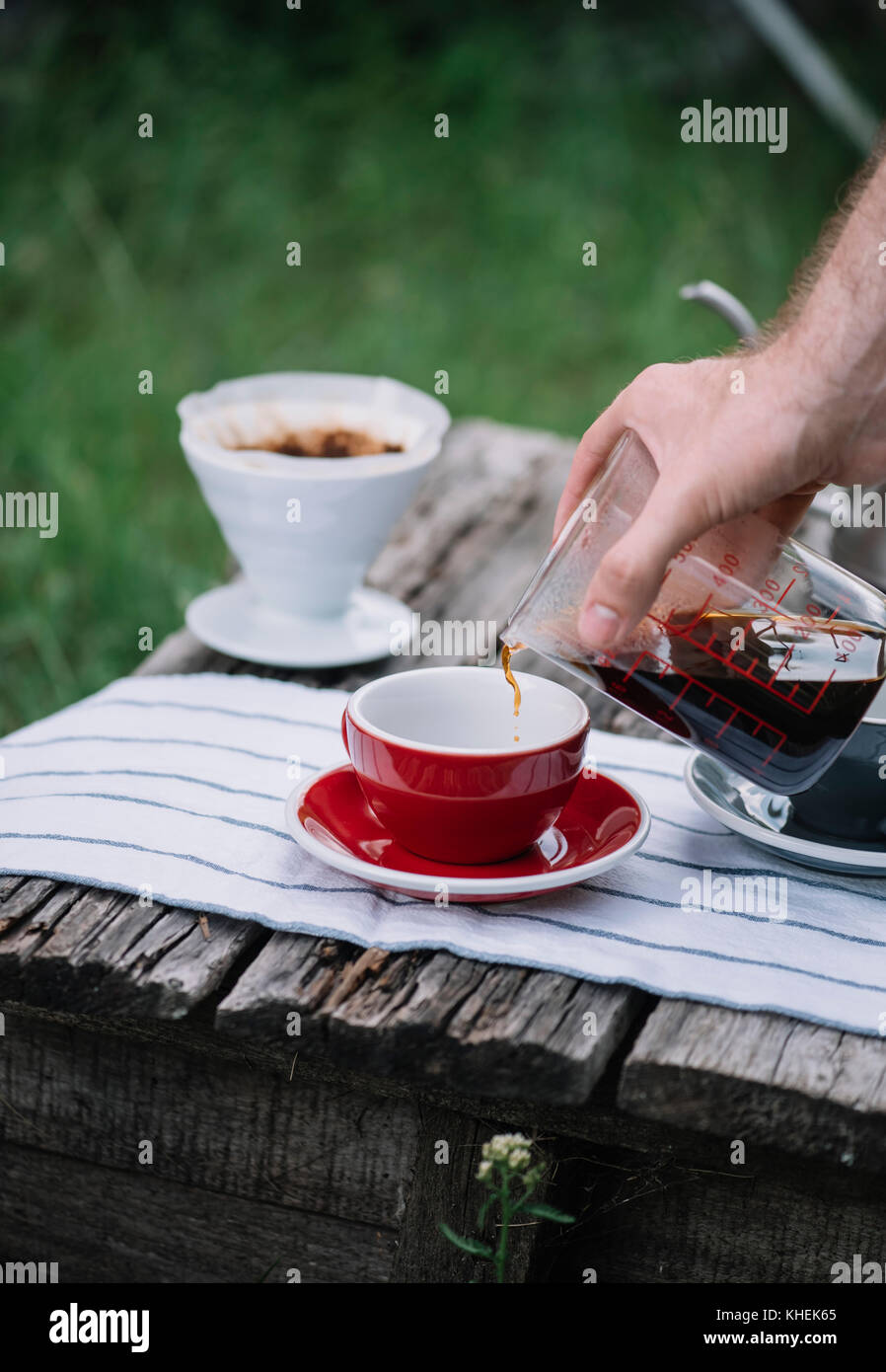 Delicious freshly brewed outdoor pour over coffee pouring into porcelain red coffee cup - Stock Image
